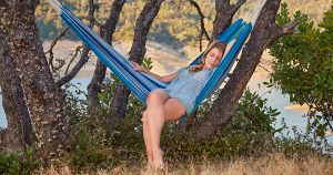 A barefoot woman resting in a hammock on a hill above a mountain lake in Northern California.