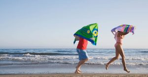 Two kids with microfiber beach towels running by the ocean