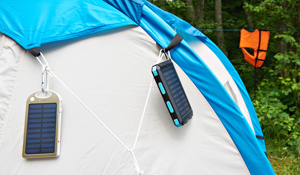 Solar panel USB chargers hang on a tent in a camp site.