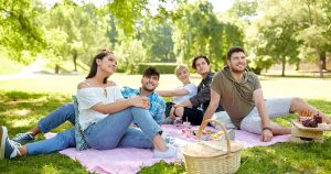 College students enjoyinng an outdoor picnic on a big blanket. Modern picnic blankets and mats have great features that make them a great asset on camping or beach trips.